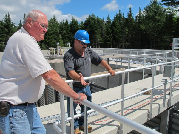 Dave Hardy (left), project inspector for Portland engineering firm Woodard & Curran, and Ellsworth Wastewater Superintendent Mike Harris look over an aeration tank at Ellsworth's new waste water treatment plant. The facility is expected to be complete by this fall, and will double the city's treatment capacity and, the city hopes, eliminate the discharge of untreated water into the Union River.