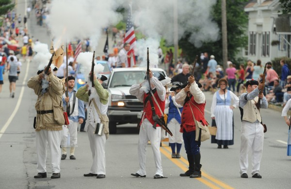 Members of McCobb Co., a civil war re-enactment group, fire muskets along Wilson Stret in Brewer as part of the Bangor-Brewer Fourth of July parade on Wednesday.