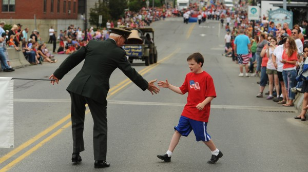 Junior Tracy, a World War II, veteran shakes hands with a young boy along the Fourth of July parade route in Bangor on Wednesday.