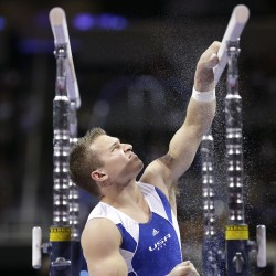 Jonathan Horton rubs chalk on the parallel bars while preparing to compete during the preliminary round of the men's Olympic gymnastics trials in San Jose, Calif., on June 28.