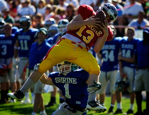The East's Adam Odgen, representing Maine Central Institute, makes a leaping interception over the West's Samuel Chaves, representing Massabesic High School, in the 23rd annual Maine Shrine Lobster Bowl Classic in Biddeford Saturday July 21, 2012.