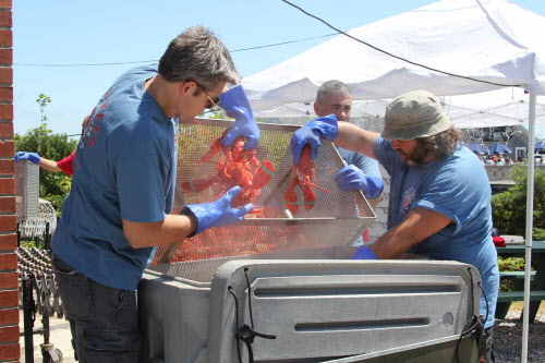 Volunteers haul lobster out of steaming ovens at the Maine Lobster Festival in Rockland in August 2011.