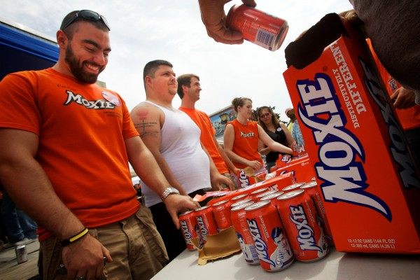 Kurt Banker (left) of Glassboro, N.J., looks down at his assembled 12-pack of Moxie before the start of the annual Chugging Challenge at the Moxie Festival in Lisbon Falls Saturday, July 14, 2012.