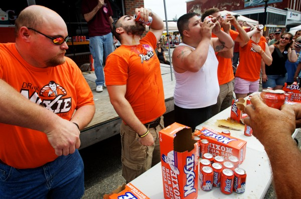 Contestants in the Chugging Challenge at the Moxie Festival in Lisbon Falls Saturday, July 14, 2012, see who can drink the most cans of Moxie, Maine's official soft drink, in two minutes. Competing are (from left) Beau Bradstreet, Kurt Banker, Buddy Edwards, Freddie Stahl and Ashley Fish. The hands of the sixth contestant, Andrew Higgins, can be seen at right.