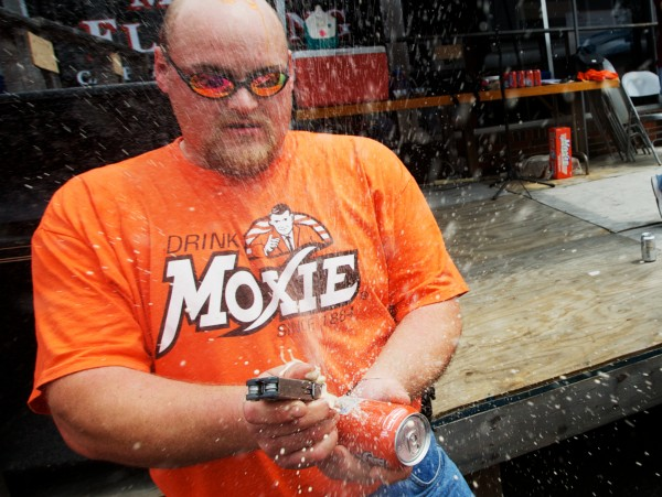 Beau Bradstreet of Bridgewater pokes a hole in a can of Moxie before shotgunning it during the annual Chugging Challenge at the Moxie Festival in Lisbon Falls Saturday, July 14, 2012.