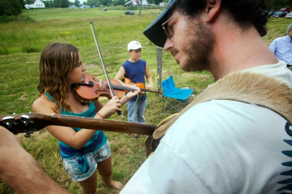 Eric Dayan tunes his guitar backstage at the 40th annual East Benton Fiddlers Convention Sunday, July 29, 2012 while Helen Newell, 12, and John Hachey, 13, get ready to compete. Newell went on to win the under-15 division.