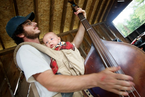 Eric Dayan picks up the bass while jamming onstage at the East Benton Fiddlers Convention Sunday, July 29, 2012 with his infant son, Benton, strapped to his chest.