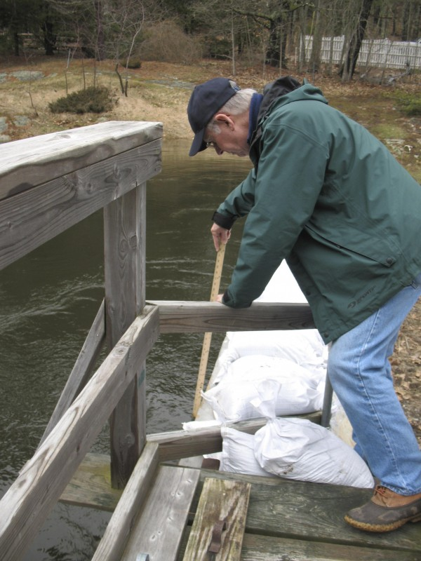 Ken Bailey measures how fast the water is rising on Lake Megunticook in 2009 while service as the dam control agent for Camden.