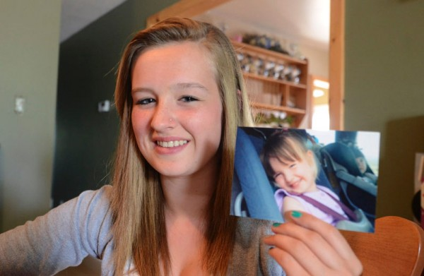 Taryn McKee holds a photo of herself Tuesday, July 3, 2012, from when she was 3 years old. A message her mother wrote for her that was tossed in the Atlantic when the family was on vacation 12 years ago recently was found on an island in Maine.