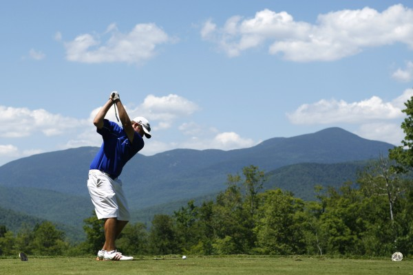 The Mahoosuc Range looms in the backgrounds as Seth Sweet hits a tee shot on No. 14 during the Maine Amateur Championship at Sunday River Golf Club, Thursday, July 12, 2012, in Newry, Maine.