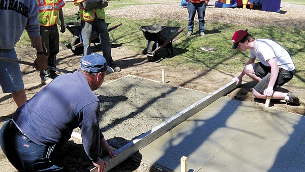 Brewer Boy Scout Mason Duplissie (right) and Dan Godin of Godin's General Contractor Inc. smooth the concrete poured for a new picnic table shelter for the Brewer Public Library.