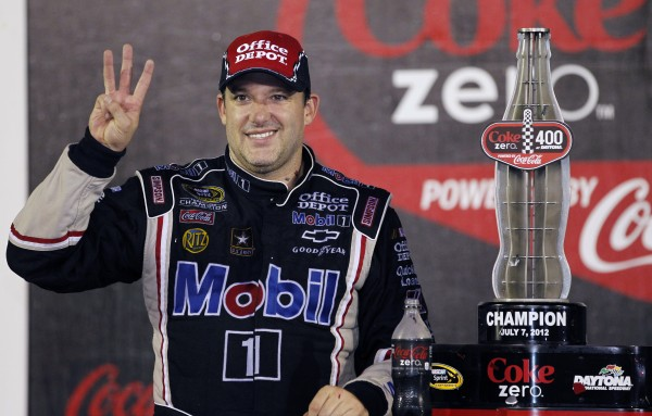 Tony Stewart hold up three fingers to signify winning the summer NASCAR Sprint Cup Series auto race for the third time at Daytona International Speedway on Saturday, July 7, 2012, in Daytona Beach, Fla.
