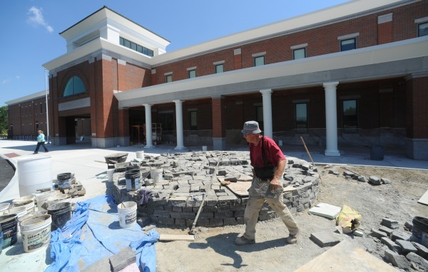 Stone mason Jamie Leonard, member of Hampden Academy's Class of 1964, walks around the base he is constructing with Corinthian granite for the new Bronco sculpture that will grace the front walkway at the new Hampden Academy school complex.