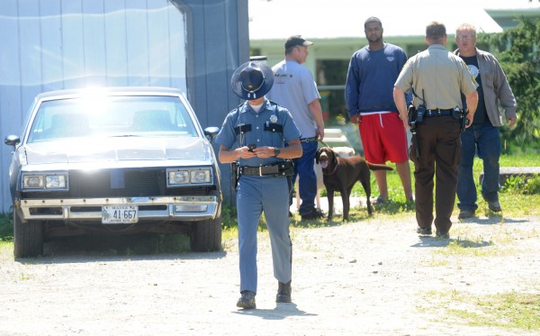An officer with the Penobscot Sheriff's Department speaks with residents at the property on the Johnson Mill Road in Orrington on Sunday morning.