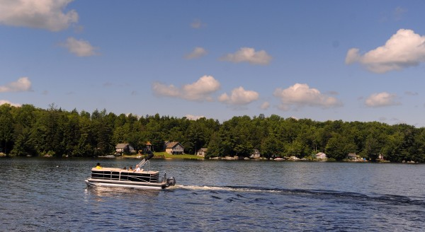 The Dunn family rides on their pontoon boat on Beech Hill Pond in Otis in July 2012. &quotThese boats are very popular, we can see about eight or nine others just from our dock,&quot Jim Dunn said.