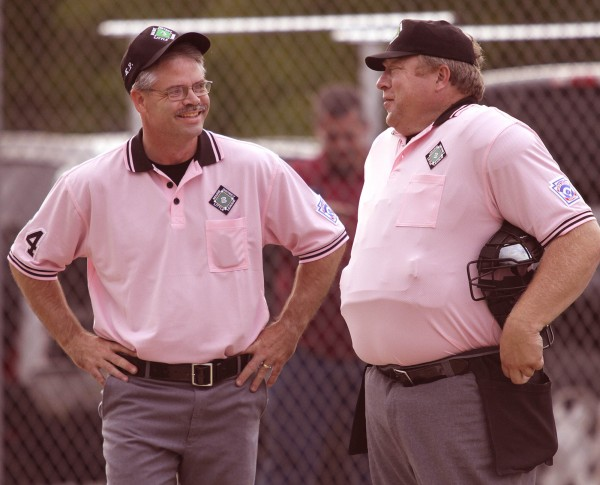 Bangor District 3 Little League umpires Troy Lare (left) and Chris Parker share a light moment between the second and third inning of an all-star baseball game last season in Bangor. Parker is in Kutno, Poland, this week to umpire in the European Little League Baseball Championships.