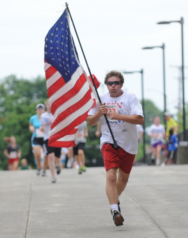 Timothy Page of Bangor carries Old Glory  as he kicks to the finish of the 32nd annual Walter Hunt Memorial 3K road race Wednesday, July 4, 2012.  Page said he has run the race since 1992 and this is the third time he has carried the U.S. flag in the race.