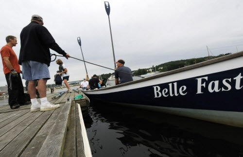 Race coordinator Malcolm Gater of Belfast holds a line to the team's Cornish pilot gig, the Belle Fast, as the crew gets ready to offload after a training session in Belfast harbor Thursday evening, July 26, 2012. On the far left is crew member John Dillenbeck of China.