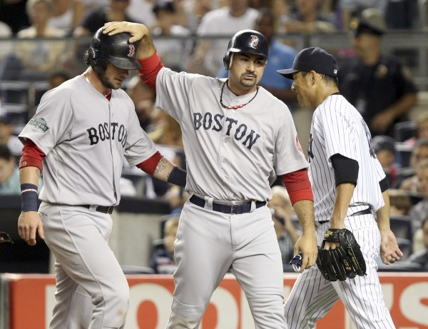 Boston Red Sox's Jarrod Saltalamacchia, left, and Adrian Gonzalez, center, celebrate scoring on a double by Ryan Sweeney while New York Yankees' pitcher Hiroki Kuroda returns to the mound during the second inning of a baseball game at Yankee Stadium in New York, Sunday, July 29, 2012.