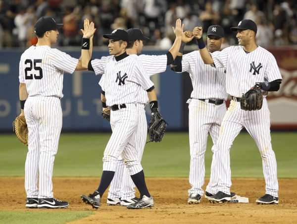 New York Yankees' Ichiro Suzuki, second from left, celebrates with teammates Mark Teixeira, left, Jayson Nix, third from left, Robinson Cano, second from right, and Derek Jeter after a baseball game against the Boston Red Sox at Yankee Stadium in New York, Friday night, July 27, 2012. The Yankees defeated the Red Sox 10-3.