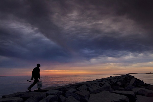 A fisherman heads out to fish for mackerel and striped bass on the Camp Ellis Jetty as unsettled weather overtakes the sky Friday, June 29, 2012, in Saco. A few minutes later the first rainstorm of the day broke out.