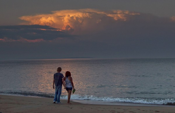 A couple watches a cloud formation at Ferry Beach Friday, June 30, 2012, in Saco.