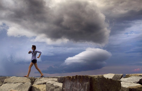 A young lady hurries off the rocks at Camp Ellis jetty as a thunderstorm blows by to the north Sunday, July 1, 2012, in Saco.