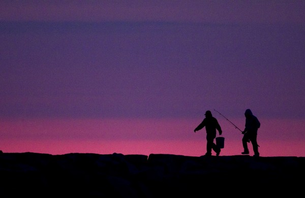 Fishermen walk along the Camp Ellis jetty a half hour before sunrise as the first light of dawn colors the eastern horizon Friday, June 29, 2012, in Saco.