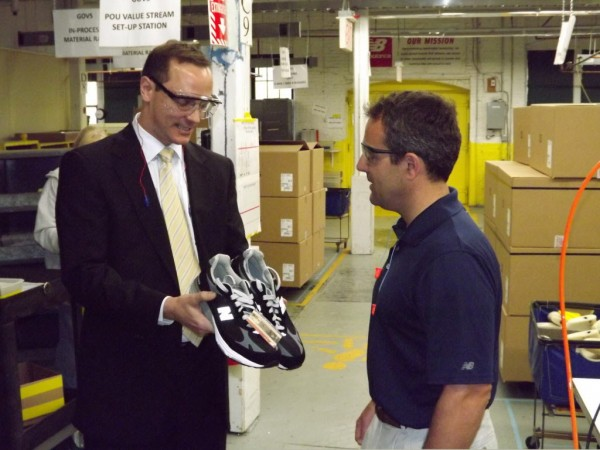 Paul Piquado (left), Assistant Secretary of Commerce for Import Administration, accepts a pair of shoes from New Balance Skowhegan Plant Manager Patrick Welch during a tour of New Balance's Skowhegan facility last month.