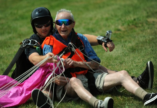 90-year-old Lester Slate of Exeter (right) sits on the ground with tandum skydiving instructor Matt Riendeau after jumping from an airplane at 10,000 feet for his 90th birthday at Central Maine Skydiving in Pittsfield on Sunday, July 15, 2012.