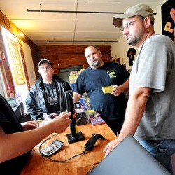"Jay Blais, co-owner of Patriot Fireworks in Monmouth, shows Lewiston residents (from left) Jacob Mottram, 11, with his father, Jason Mottram, and Greg Morin how to safely use a canister shell firework on Tuesday afternoon. ""You should designate a shooter for your Fourth of July parties just like you would a driver,"" said Blais. ""Alcohol and fireworks do not mix."""