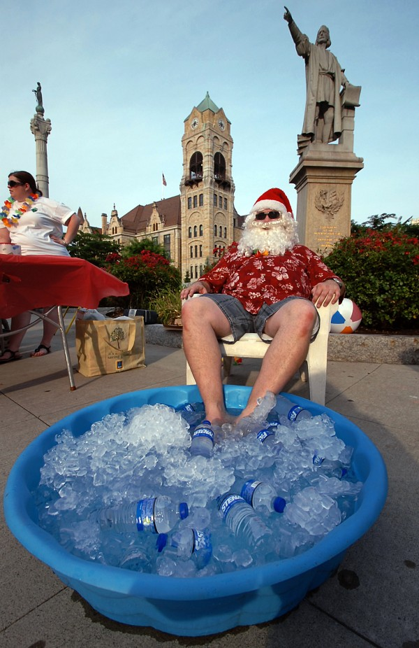 Summer Santa Claus Tom Osborn of Taylor, Pa., a member of the Greater Scranton Jaycees, cools his feet in a pool of ice at Lackawanna County Courthouse Square during First Night festivities held in downtown Scranton, Pa., on Friday, July 6, 2012.  (AP Photo/The Scranton Times-Tribune, Butch Comegys)