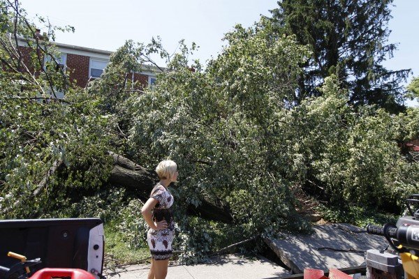 A pedestrian takes a look at downed trees blocking the entrance of a house in Baltimore on Monday after a severe storm swept through the region  late Friday. Power outages left many to contend with stifling homes and spoiled food over the weekend as temperatures approached or exceeded 100 degrees.