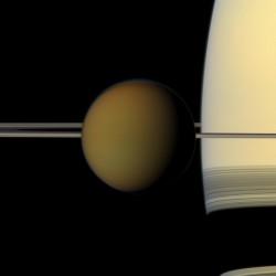 Saturn looms behind its moon Titan.