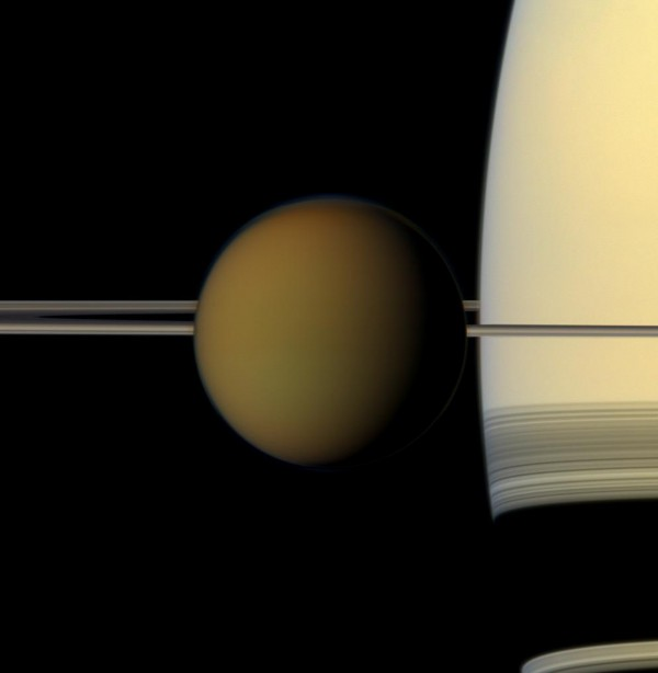 Saturn looms behind its moon Titan.