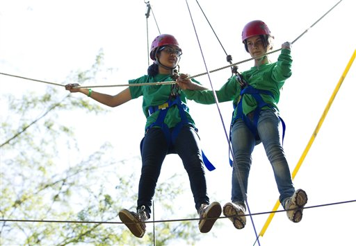 Zahra (left) of Pakistan and Marwa of Afghanistan work together to traverse a high ropes course at the Seeds of Peace summer camp in Otisfield on Wednesday, July 11, 2012.