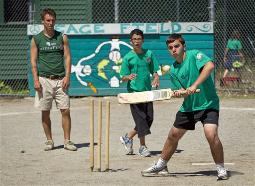 Daniel of Israel (right) swings at a ball during a game of cricket at the Seeds of Peace summer camp in Otisfield on Wednesday, July 11, 2012 . Eitan, a camper from London (center), and counselor Marcus Goldman of Cape Elizabeth look on.