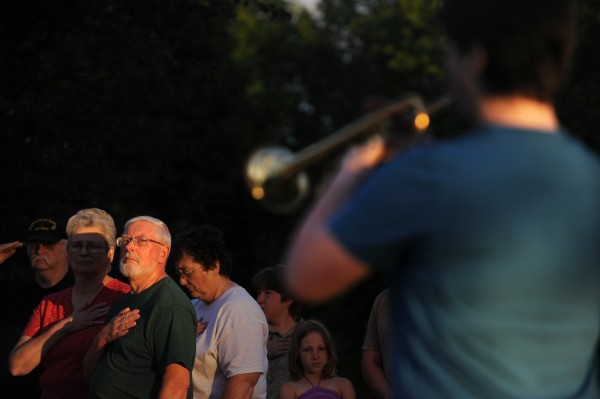 John Clark (from left), Debbie Harvey, Robert Harvey, Bonnie Clark and others stand at attention as Kristen Daigle (right), 18, of Brewer plays taps on her bugle at Holden's veterans memorial at 7:30 p.m. Monday, July 2, 2012.