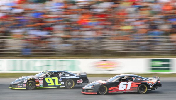 Joey Polewarczyk Jr., and T.J. Brackett of Buckfield fly past the fans in the back stretch during the middle stages of Sunday night's TD Bank 250 at Oxford.