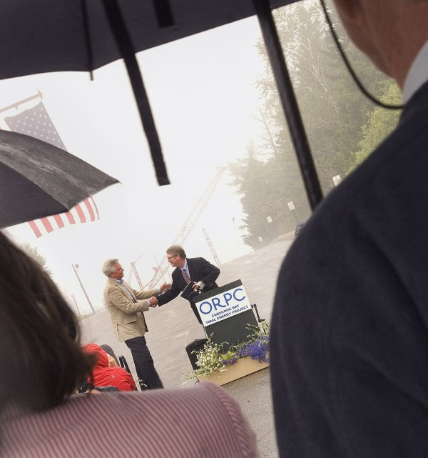 Periods of rain did not dampen the mood as Chris Sauer (left), president and CEO of Ocean Renewable Power Co., is congratulated by Sean O'Neill, president of Ocean Renewable Energy Coalition, on the successful development of the first tidal power project in the U.S., in Eastport Tuesday, July, 24, 2012.