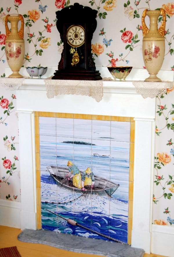 The hearth of George Chandler's parlor in his Jonesport home now showcases an art-on-tile rendition of a Chandler family historic photo that depicted George and a grandson hauling a net brimming with cod into a dory.