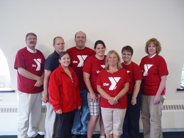 Penobscot County employees on Team Hoo-Rah celebrate losing more than 199 pounds on Wednesday as part of the Bangor Y's Biggest Mover program. From left to right are Lewis Beal (back row), Bill Collins, Brian Kinley, Trainer Ami Bisacre, Holly Page, Cindy Collins, Ami Picard (front row) and Dianne Caine. Absent from the photo were Scott Atkins and Althea Baker.