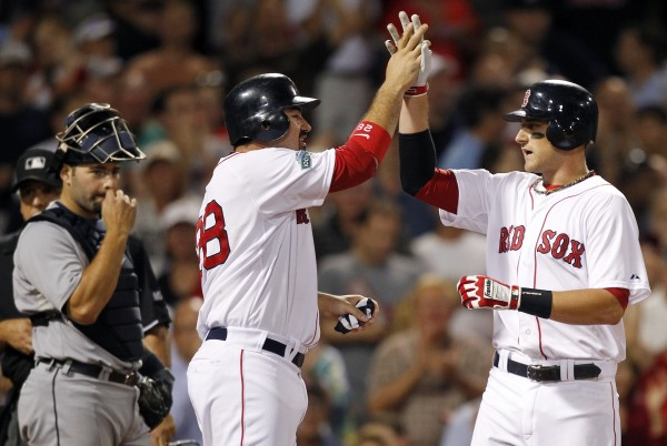 Boston Red Sox's Will Middlebrooks, right, celebrates his two-run home run that also drove in Adrian Gonzalez, center, as Detroit Tigers' Alex Avila, left, watches in the eighth inning of a baseball game in Boston, Monday, July 30, 2012.