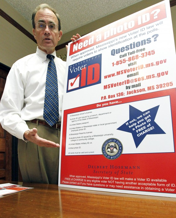 Secretary of State Delbert Hosemann displays one of more than 1,000 signs that have been posted throughout the state informing voters on photo IDs for voting in Jackson, Miss on Tuesday, June 19, 2012.