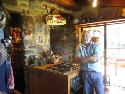 Thom Hope stands in the kitchen of the home he built for himself in the 1980s. The tile set into the stone wall came from Portugal and has been dated back to the 1600s.  Thom and a friend rescued the tile from an old building in Portugal, just before it was taken down by a wrecking ball.
