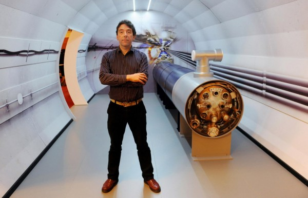 University College London professor Jon Butterworth, a scientist on the Atlas experiment, stands with a model of the Large Hadron Collider in London, England on Wednesday, July 4, 2012.