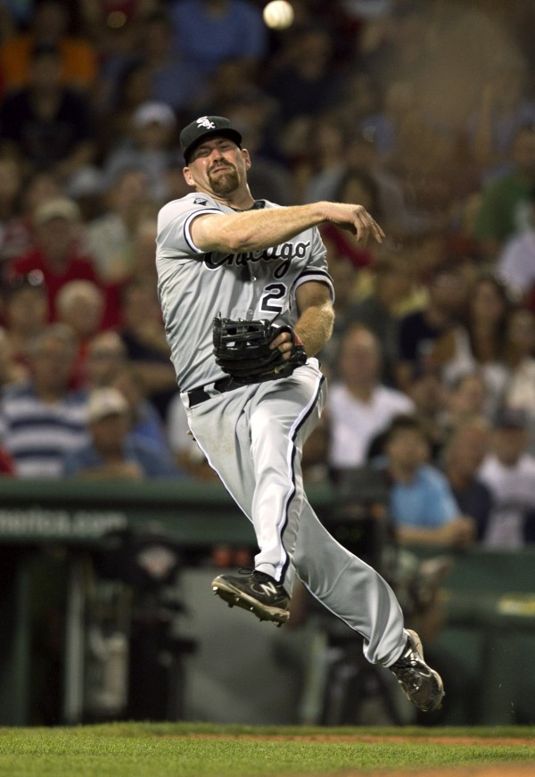 Chicago White Sox's Kevin Youkilis throws to first in an attempt to retire Boston Red Sox's Carl Crawford in the eighth inning of a baseball game at Fenway Park in Boston, Tuesday, July 17, 2012.