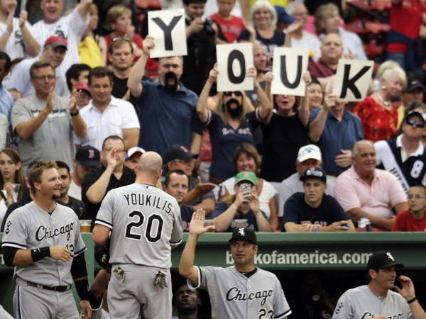 Chicago White Sox third baseman Kevin Youkilis is congratulated by teammates and fans after scoring on a throwing error during the first inning of a baseball game against the Boston Red Sox at Fenway Park in Boston, Monday, July 16, 2012. Youkilis returned to Fenway, where he was a member of the 2004 and 2007 World Series Champion teams, for the first time since being traded.