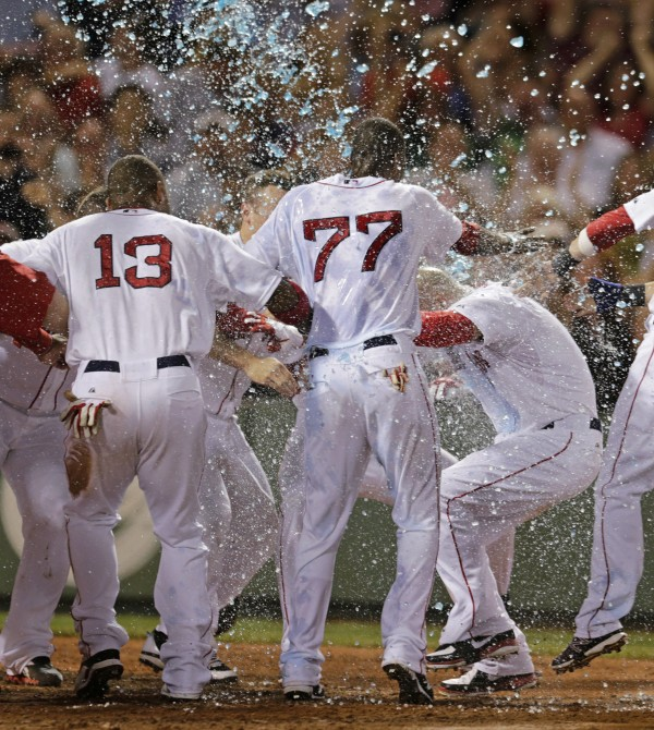 Boston Red Sox's Cody Ross is doused by his teammates as he crosses home plate on his game-winning home run in the ninth inning of a baseball game against the Chicago White Sox at Fenway Park in Boston, Thursday, July 19, 2012. Ross' three-run homer gave Boston a 3-1 win.