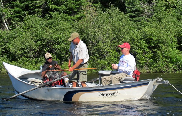 U.S. Army Sgt. Tim Pierre of Oakland, Calif., holds up a landlocked salmon as guide Chad Cray (center) and Army Capt. Stan Wells, of Baxter Springs, Kan., look on during a drift boat trip on the East Outlet of the Kennebec River on Wednesday, July 11, 2012. Five soldiers who are receiving treatment at Walter Reed Army Medical Center were in Maine for three days of fishing as a part of a Wounded Warrior Outdoors trip.